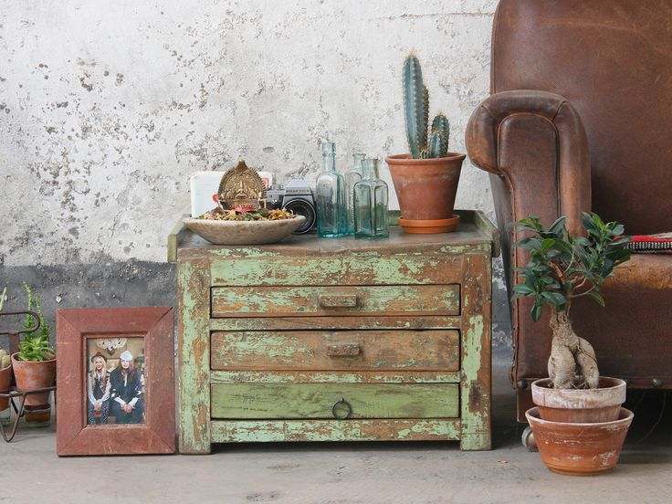 A compact Vintage Side Table with 3 drawers, its original distressed and faded paint finish. There's nothing better than time worn wood - the top shows the marks left by the jewellery maker's tools as he worked to make gold and silver jewellery. Today the table makes a striking side table or bedside table