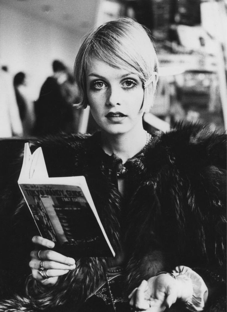 """Twiggy reading Tokyo Handy Guide.  By blending pop art with fashion, the doe-eyed, pouty-lipped gamin with the angelic puss and boyish crop took the industry by storm at age 17 defining the age of """"flower power"""" almost singlehandedly. She forever replaced the voluptuous image of what modeldom had once been all about. She originally was nicknamed """"Sticks"""" because of her reed-thin figure, but then switched it to """"Twigs"""" and, finally, """"Twiggy."""""""