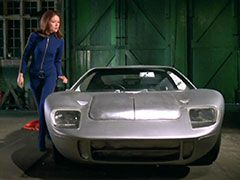 Mrs Peel circles the silver Ford GT40 warily after finding it in Primble's garage, she is wearing her navy catsuit