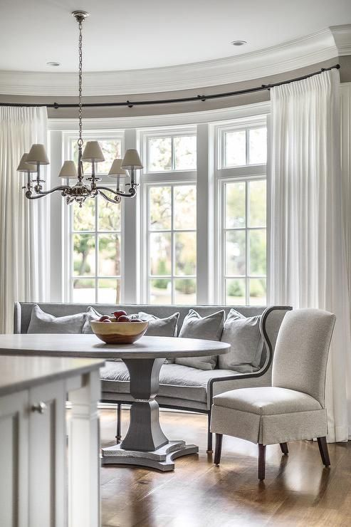White curtains cover windows framed by a gray wall and positioned behind a curved dining settee topped with gray pillows and positioned beside a light gray skirted dining chair facing a white and gray oval pedestal dining table.