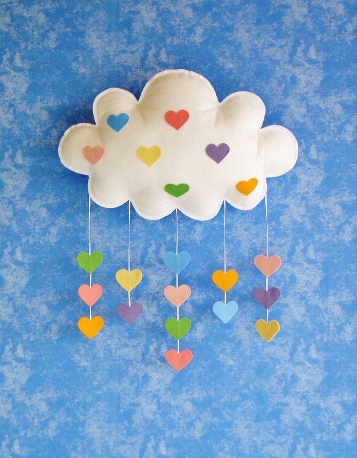 Uma linda nuvem com gotinhas de coração nas cores do arco íris !    Perfeita para decoração de festas com tema de nuvens ,céu , balões , arco íris e para decoração do quarto !    Confeccionada em feltro liso , vem com uma argola para fixação em parede .    Mede 49 cm de comprimento e 31 cm de alt...