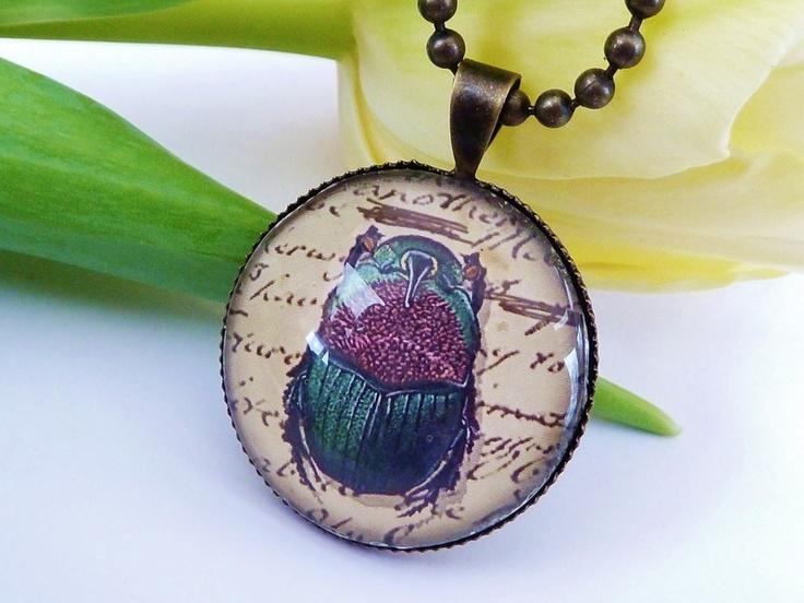 Der Anhänger besteht aus bronzefarbenem Metall (nickelfrei), der Glas-Cabochon ist handgearbeitet und zeigt ein schönes Motiv mit Skarabäus.  Der D...