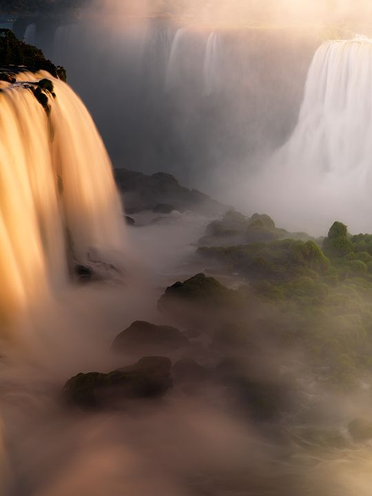 The swirling waters of the Iguazu River tumble into the sunset mist of the rainforest, Argentina