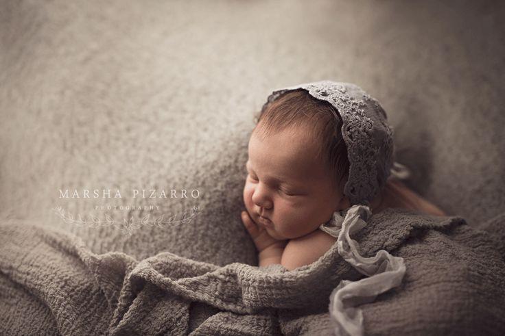 newborn baby girl on grey backdrop in bum up pose wearing matching bonnet