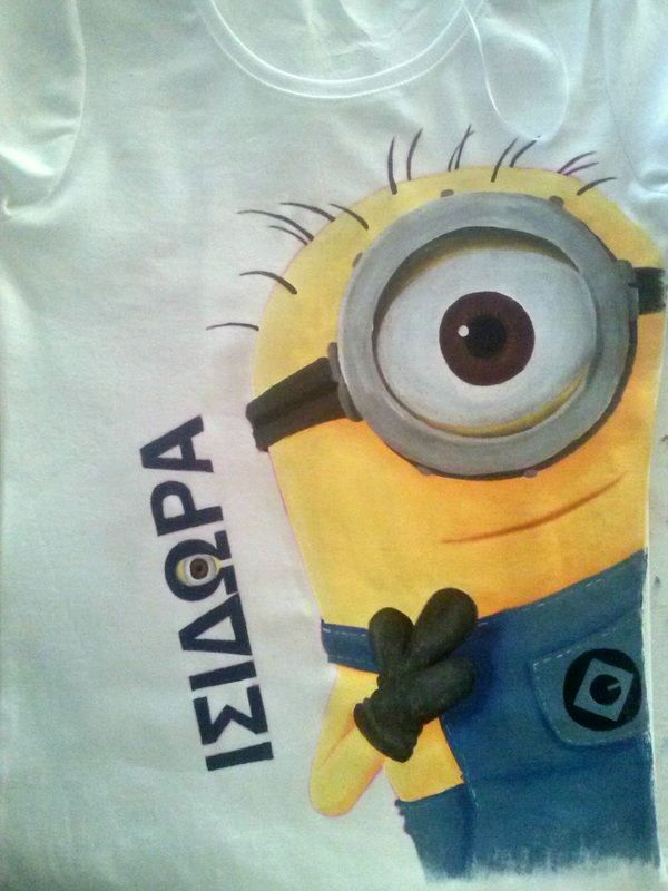 """Hand painted girl's t shirt, featuring a Minion from the """"Despicable Me"""" movie. The girl's name (Isidora) is written in Greek. The colors are non-toxic, water based, permanent fabric colors."""
