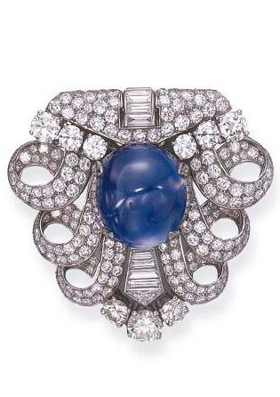 AN ART DECO DIAMOND AND SAPPHIRE BROOCH, BY BULGARI  Centering upon a cabochon sapphire, weighing approximately 44.80 carats, within three pavé-set diamond openwork scrolls, enhanced by baguette and circular-cut diamonds, circa 1930 Signed Bulgari