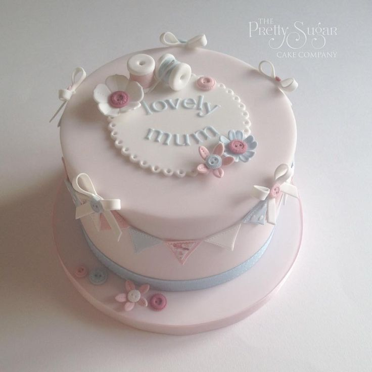 Pink sewing theme birthday cake with cotton reels, buttons, bunting and blossoms detail
