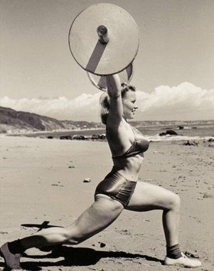 Abbye 'Pudgy' Stockton with a split snatch on the beach. She was a pioneer in womens' weightlifting, organising the first sanctioned contest in 1947.
