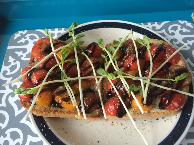 Vogel's 6 seed gluten free toast with cherry tomatoes, crushed garlic, S&P, balsamic reduction and snow pea shoots.