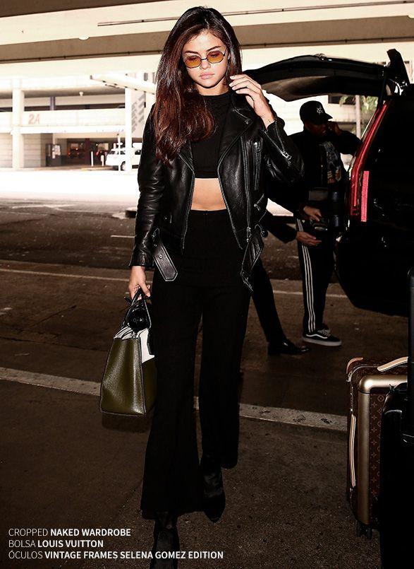 Look de aeroporto da Selena Gomez com blusinha cropped preta, calça com boca larga e jaqueta de couro