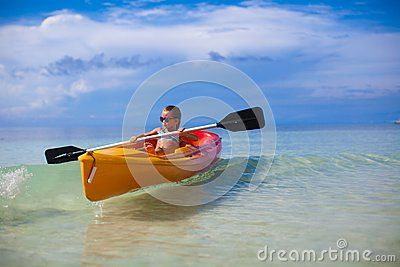 Little cute girl rowing a boat in clear sea. This image has attached release.