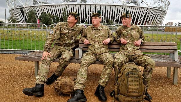 Soldados do Regimento Real da Escócia descansam em frente ao estádio olímpico.