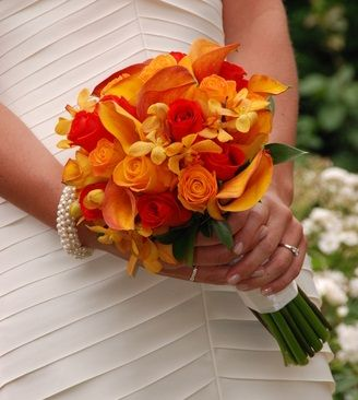 A beautiful bouquet or orange and vermillion roses, with mango calla lilies and yellow orchids.