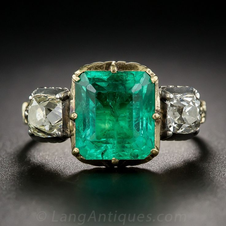 Georgian Foil-Backed Emerald and Diamond Ring. A rare and wonderful antique gem, dating from the early-19th century. A gorgeous green Colombian emerald, weighing approximately 2.50 carats, is accompanied right and left by a sparkling antique cushion-cut diamond. The emerald casts an extra glow due to the foil-back setting (so it is not to be submerged in water), and the pair of diamonds are set in silver bezels. A fluted under gallery and fancy shoulders ...
