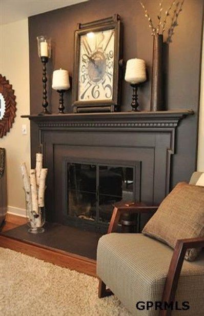 Dark wall, clock, candle holders vase on mantel-- birch logs on hearth