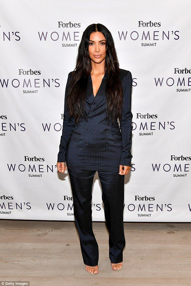 She means business! Kim Kardashian slips into a pinstripe power suit (with plunging neckline) for a spot at the Forbes Women's Summit