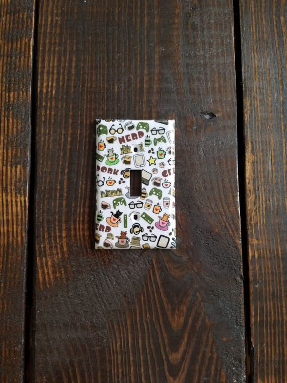 What do you find in every home that's exactly the same? Light switch and electrical outlet covers. Why not add a little personality to your home with decorative covers designed to match your rooms' décor.  This eclectic nerd/dork shout out piece is both hilarious and adorable! Youll find everything your nerdy heart loves; cats, coffee, books, electronics, video games, glasses, and more. This would be perfect for a; bedroom, bathroom, game room, craft room, kids room, teen room - or any r...