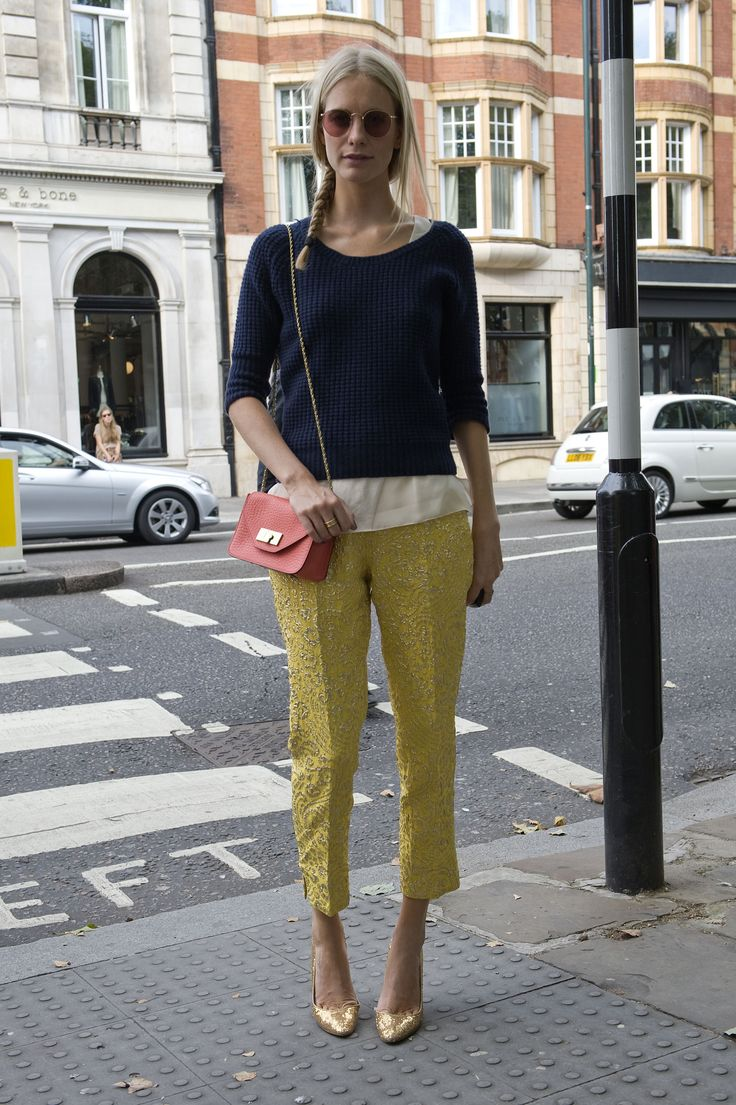 Poppy Delevingne styled up an understated play on embroidered trousers and metallic heels, adding in a classic knit topper.