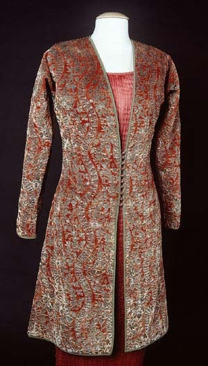 This Fortuny jacket was worn by Mrs. Harrison Williams, an American socialite who was voted in 1933 by French designers Molyneux, Lanvin, Vionnet, Lelong and Chanel as the best-dressed woman in the world. This three-quarter length orange-red cut velvet jacket was printed with metallic paints with Venetian glass buttons and silk loop closure at the center front.