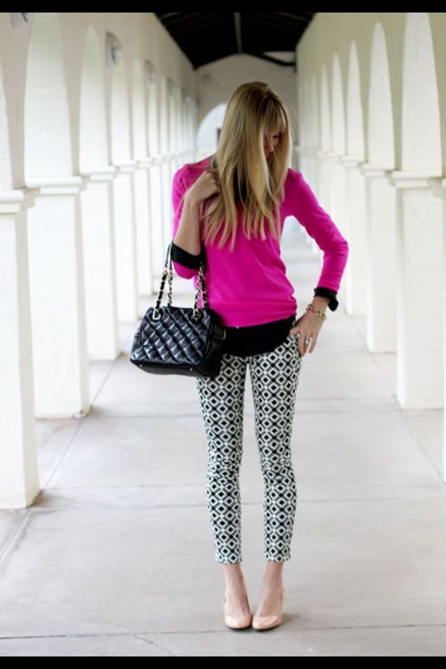 Fuchsia sweater with layered black top, patterned trousers, and nude ballet flats.