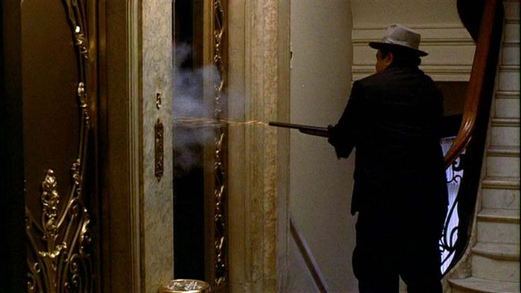 """Corleone family caporegime Peter Clemenza (Richard Castellano) shoots Don Anthony """"Black Tony"""" Stracci during the Baptism Murders scene in """"The Godfather"""" (1972)."""