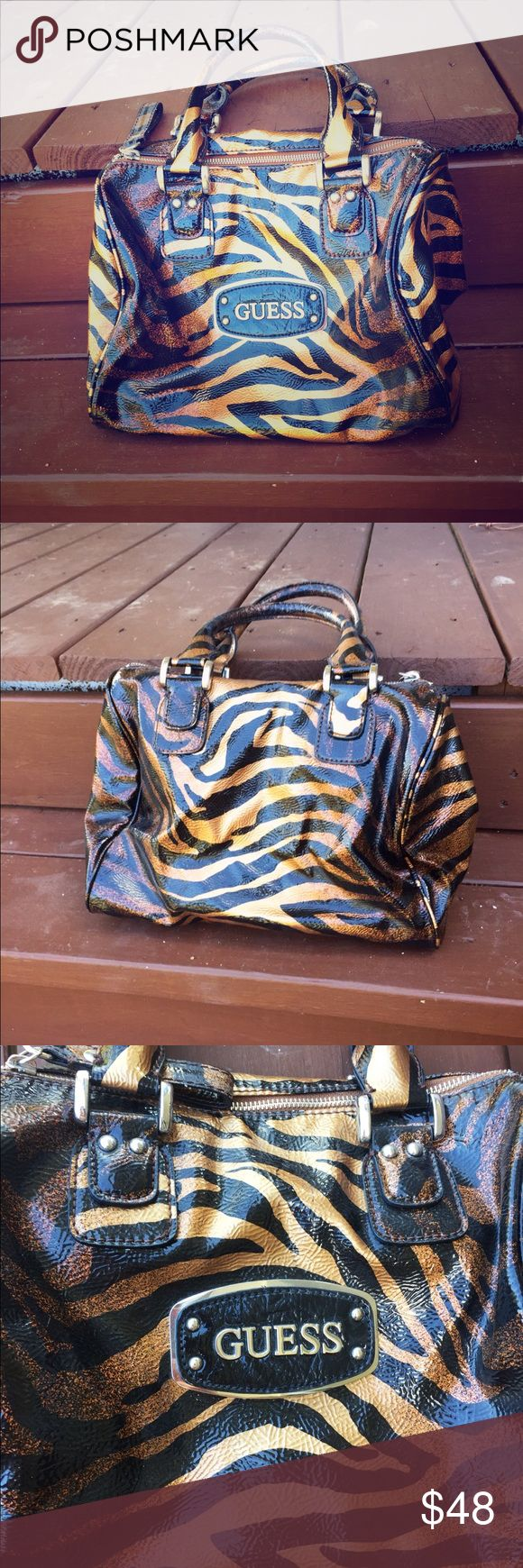 Guess Tiger Stripe Handbag Elegant hand carry purse. Authentic GUESS brand. Size of a speedy 30. Rounded handles and trimmings. Used less than a handful of times. Silver hardware. Interior of bag is in perfect condition. Please use offer button to submit offers! 💖 Guess Bags