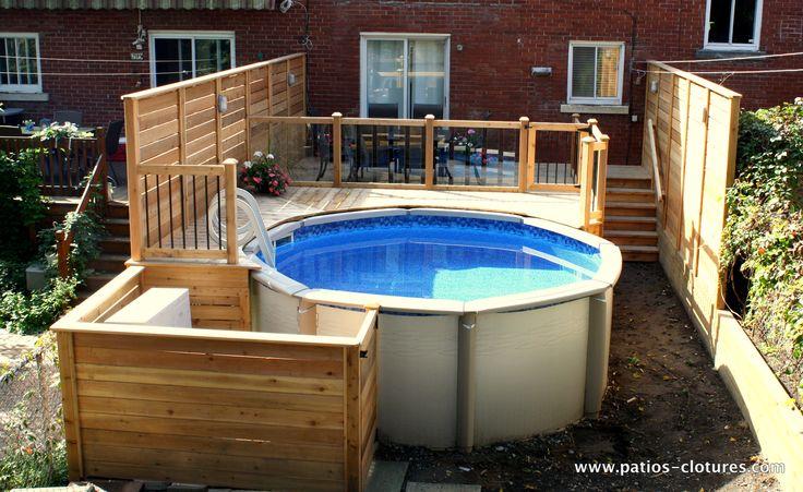 Patio de piscine hors terre Verret avec rampe de verre trempé, espace repas et écrans d'intimité.