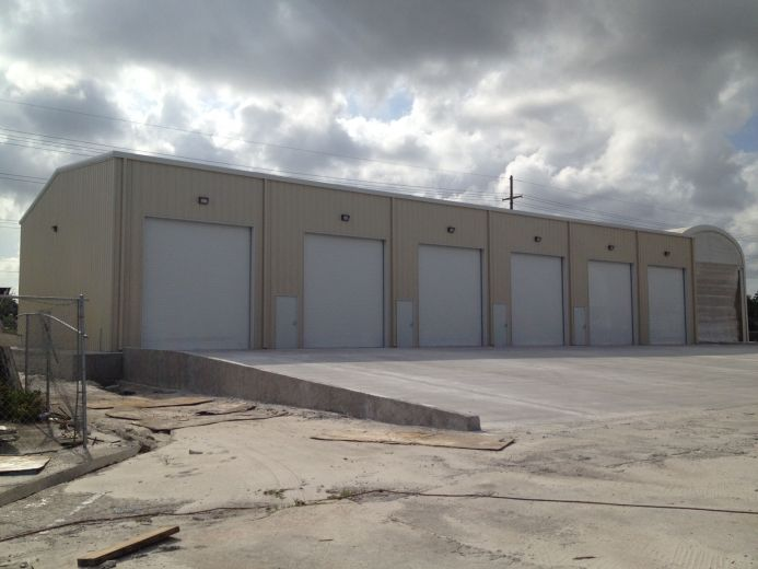 """This Marina is a pre-engineered metal structure that is 60 x 120 x 12 (1.5:12) roof pitch and is located in Dania Beach, FL.  Buck Steel designed this metal building with (6) 14 x 16 commercial roll up doors and (7) 3070 walk doors, it has 3"""" insulat"""