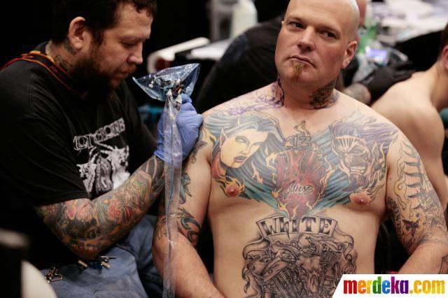 Seniman membuat tato di bahu klien pada Festival Jalan Hampton Tattoo di Virginia.