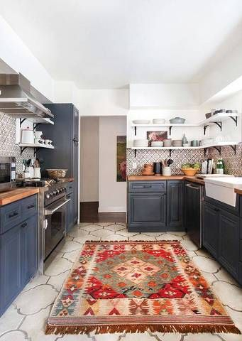 This kitchen shows off two trends – navy cabinets and the inclusion of a vintage rug.