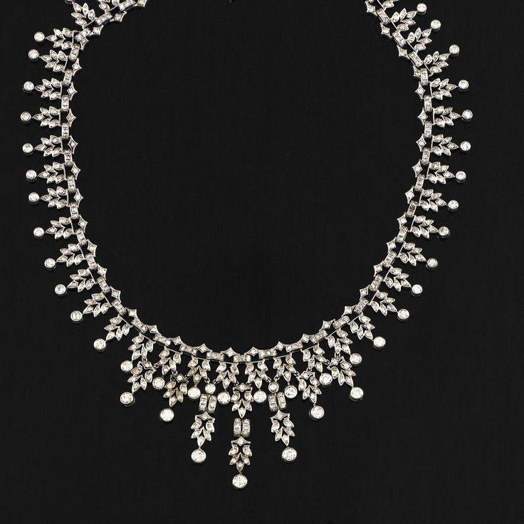 Collier in oro bianco a motivi fogliacei e geometrici pendenti impreziositi da diamanti e finiti con brillanti in castone tondo a dimensioni degradanti; gr 69; brillanti/diamanti cts 10.00 ca