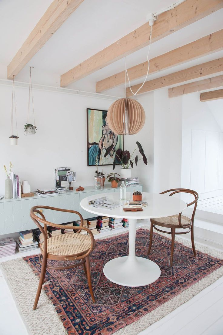 Gorgeous blonde wood beams on ceiling, tulip table, midcentury chairs and traditional rug.