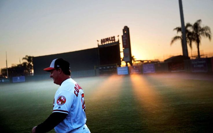 Week of Feb. 24, 2017:     Sarasota, Fla.:    Sunlight breaks through morning fog hovering over the field at the Baltimore Orioles spring training facility as coach Scott Coolbaugh  walks by to attend the baseball team's photo day on Feb. 20.