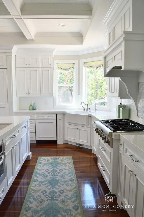 White kitchen features a coffered ceiling over white cabinets paired with white quartz countertops and a white subway tiled backsplash.