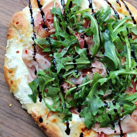 Easy, homemade, delicious pizza crust topped with prosciutto, arugula and burrata, finished with a balsamic glaze.