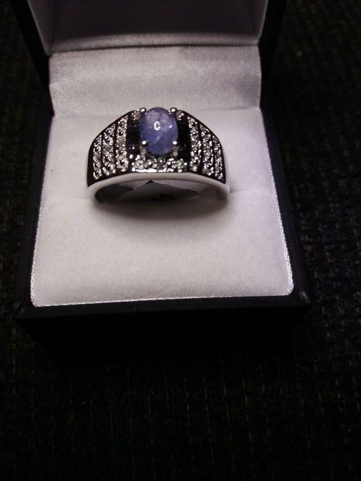 Een Distinguished 614 g zilver heren Ring met echte 1.150cts Lila blauwe Tanzanite (uit één bron) met witte topaas  Deze zeer aantrekkelijke ring bestaat uit 614 g van sterling zilver met een prachtige Tanzanite steen tussen de 12 witte topaas edelstenen. Tanzanite is razend populair vanwege het trichroic karakter wat betekent dat er drie verschillende kleuren kunnen worden gezien als we kijken naar de gem vanuit verschillende invalshoeken. In geval van Tanzanite van deze kleuren zijn blauw…
