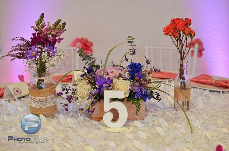 centro de mesa elegido, huacalito con botella y frasco, número de mesa en madera