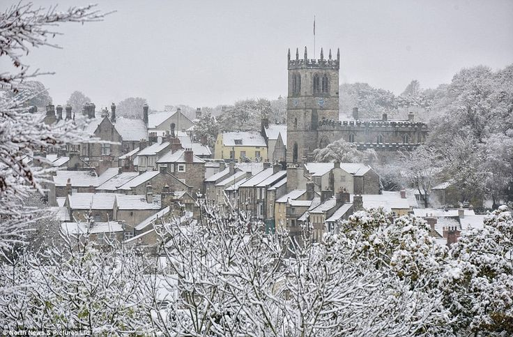 The tower of St Mary's Church in Barnard Castle, County Durham, rises above the snow-covered rooftops in the town today