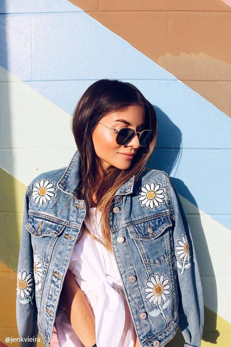 A denim jacket featuring embroidered daisy patches throughout, a basic collar, buttoned placket, buttoned chest flap pockets, front welt pockets, and long buttoned cuff sleeves.