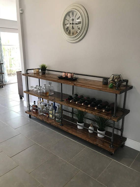 This is a beautiful industrial style bar cart made from wood and industrial pipe. Comes with wine rack that holds 7 bottles and hanging stemware racks. Dimensions approx: 80 wide x 16-1/2 deep x approx. 42 tall. Message me for customizations! Each bar cart is unique and may vary