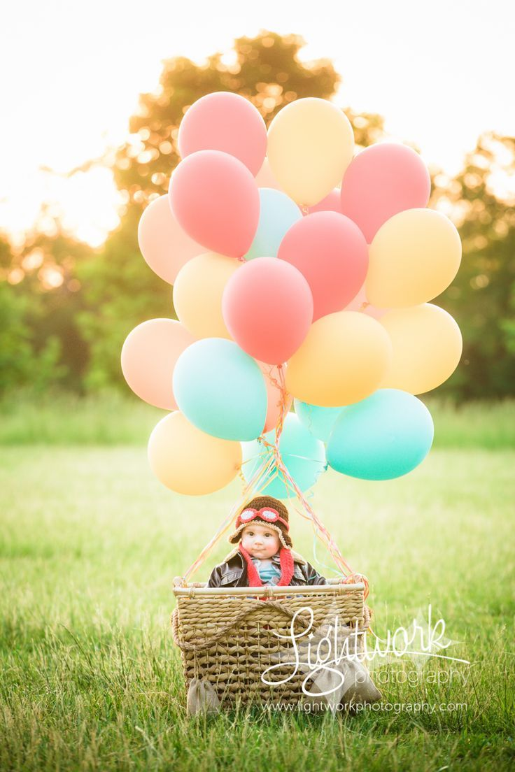 6 month old photo by Lightwork Photography, hot air balloon, balloons, aviator hat, goggles, bomber jacket, scarf, basket with sandbags, sunset, sunflare, styled photoshoot