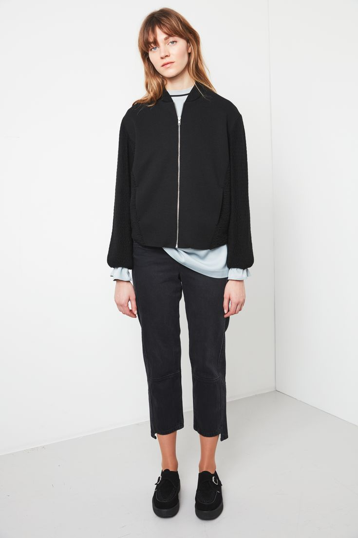 Knitted jacket style in environmentally friendly yarn in ripple knitting way. Progressive silhouette, slightly dipping down at front hem. Tight elastic at back hem creates a blousing effect for cool sculpted bomber jacket silhouette. Chunkymetal zipper adds a punky edge to the piece.