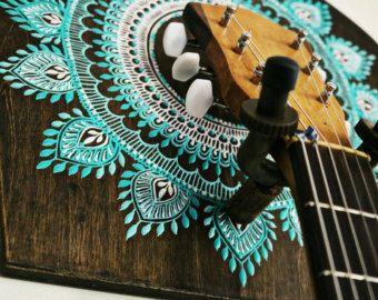 Este soporte de guitarra trae su instrumento en casa y vivir con estilo de decoración del hogar boho. Hecho a mano en California. Hecho a la medida.  tablón de madera: 14 pulgadas de alto x 10 pulgadas Hardware de suspensión de servicio pesado guitarra sostiene hasta 50 libras ras de suspensiones de la pared del pesado de montaje incluidos   Guitarra de tinte de nogal oscuro y suspensión de instrumento de cuerda adornada con un motivo de mandala de ombre pintados de mano pintados a mano…