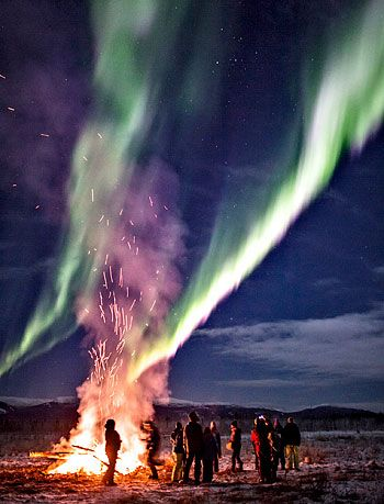 A group watches the northern lights during a bonfire on Burma Road in Whitehorse on Sunday night.