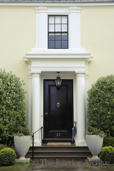 The stately Georgian facade with Doric columns and a black lacquer door give the house a sophisticated appearance