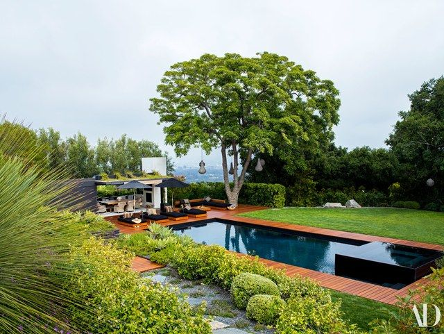 The house offers sweeping views of the city below. Marcello Villano and Anne Attinger designed the landscape. Custom teak chaise longues (on teak decking) by designer Stephen Shadley with cushions of a Perennials fabric.