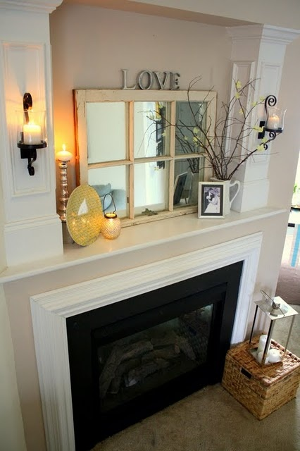 Window mirror above fireplace and sconces