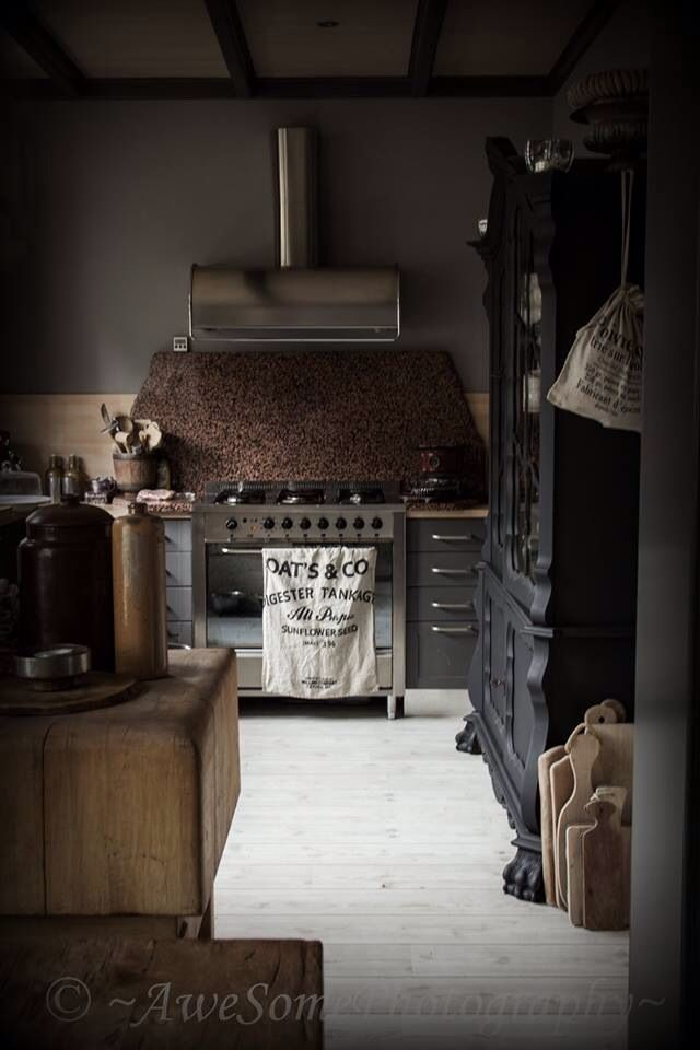 industrial extraction hood, dark stone splash back, hits of light wood and antique unit softens, light floor!