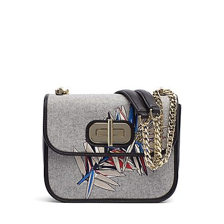 Tommy Hilfiger women's bag. Perfect for your bare essentials, our mini crossover is styled to stand out with the embroidered floral graphic. Distinguished by a gold turnlock closure and chain shoulder strap that adds to the elegant look and feel.<br>• 100% leather.<br>• 8 ¾ (L) 7 (H) 1 ¾ (W). <br>• Leather cleaner only.<br>• Imported.