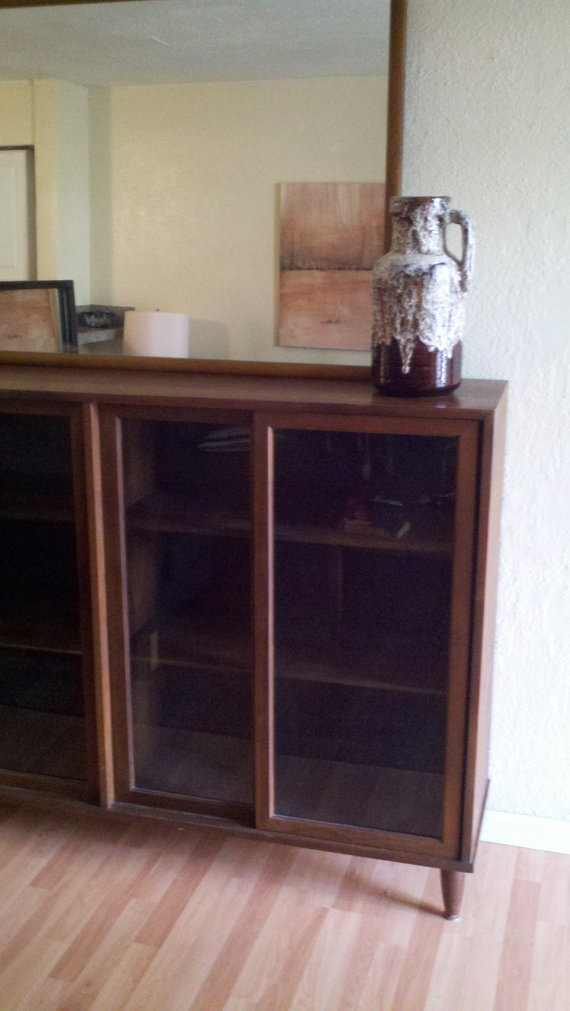 glass front bookcase on cone shaped legs by